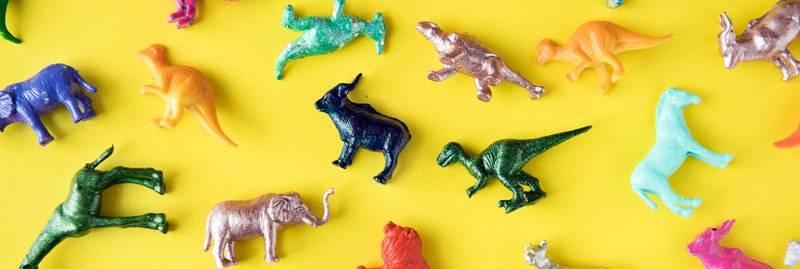 Plastik Spielzeug (Dinosaurier) auf gelbem Hintergrund